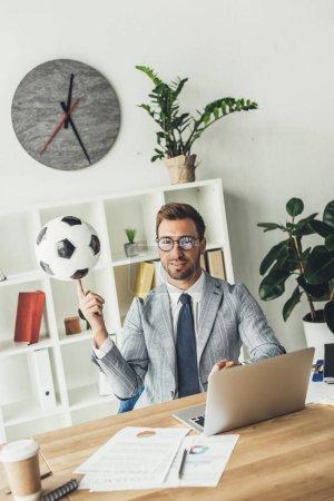 Photo pour Ballon de soccer de filature heureux homme d'affaires sur le doigt du milieu de travail - image libre de droit