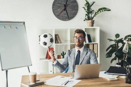 businessman spinning soccer ball on finger