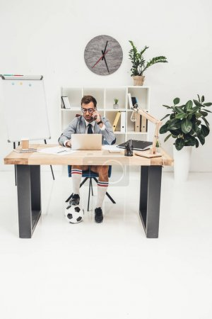 businessman in soccer shoes with ball