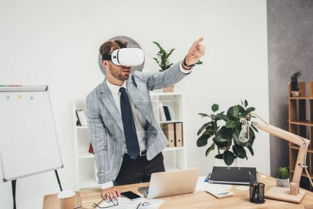 Photo for Young businessman in vr headset sitting in office pointing somewhere - Royalty Free Image