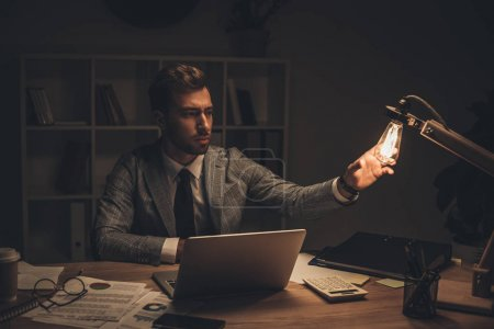 Photo for Young businessman touching table lamp at workplace on late night - Royalty Free Image