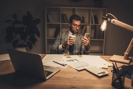 Photo for Young businessman with coffee using smartphone at late night in office - Royalty Free Image