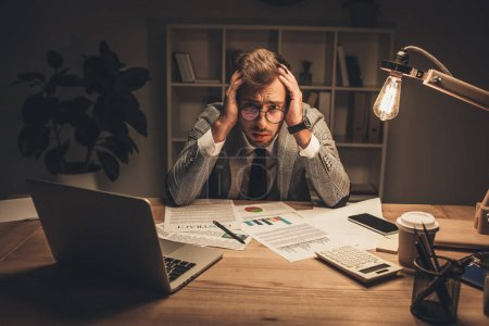 Photo for Overworked young businessman with lot of paperwork in office at late night - Royalty Free Image