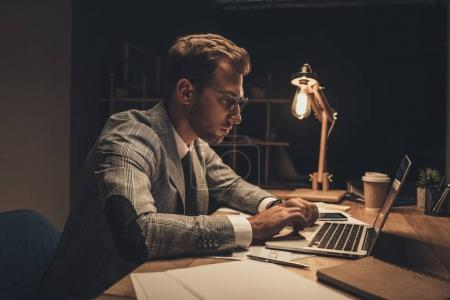 Photo for Concentrated businessman working with laptop in dark office alone - Royalty Free Image