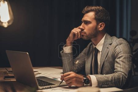 thoughtful businessman sitting at workplace