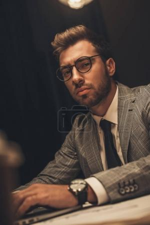 Photo for Businessman working with laptop and looking at camera at late night - Royalty Free Image