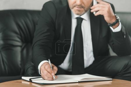 Photo pour Plan recadré d'un homme d'affaires parlant par téléphone et écrivant dans un carnet - image libre de droit