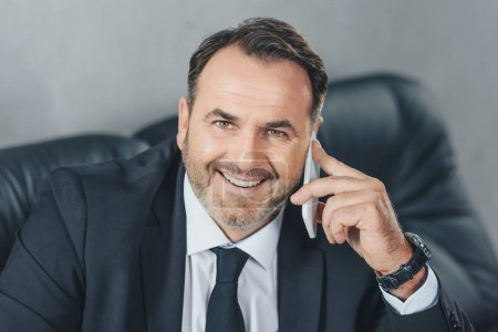 Photo for Happy mature businessman talking by phone and looking at camera - Royalty Free Image