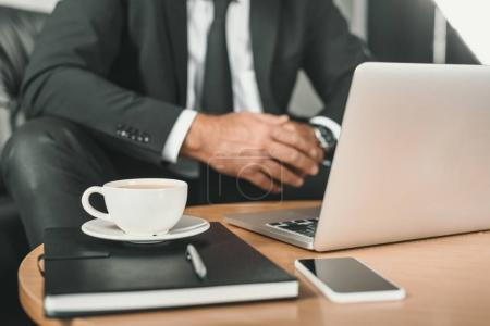 businessman with laptop and coffee on table