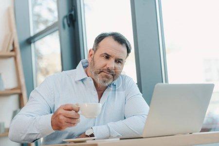 Photo pour Beau homme d'affaires mature buvant du café et regardant ordinateur portable - image libre de droit