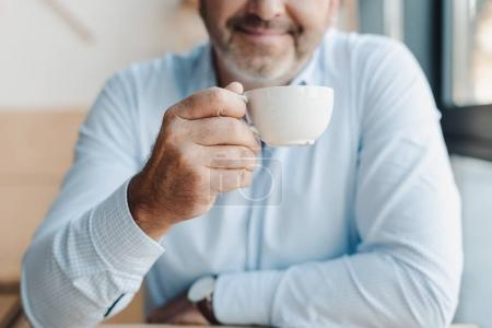 Photo for Cropped shot of mature businessman with cup of coffee - Royalty Free Image