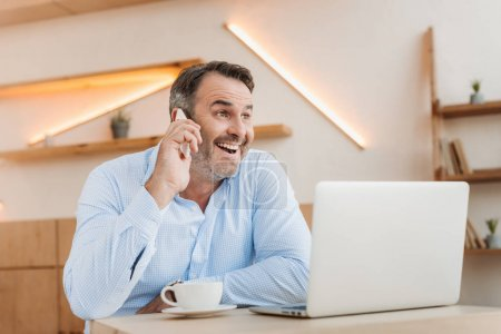 Happy businessman talking by phone in cafe