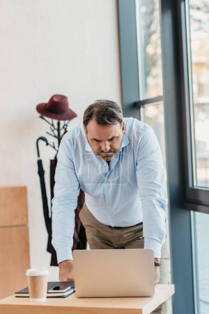 businessman looking at laptop in cafe
