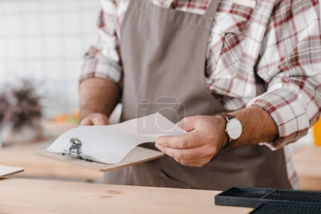 bartender checking paper on clipboard