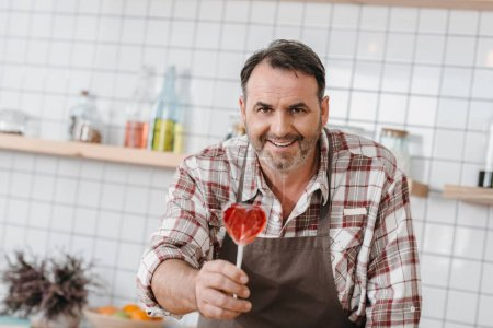 Photo for Happy mature bartender with lollypop in shape of heart at cafe - Royalty Free Image