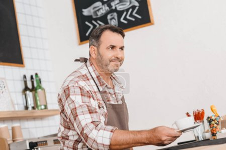 Bartender holding cup of coffee