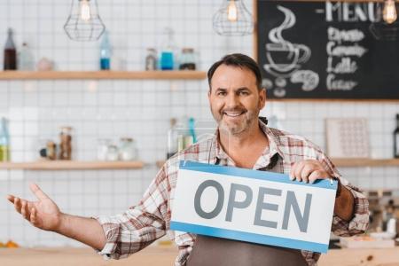 Photo pour Heureux barman mature avec enseigne ouverte au café - image libre de droit