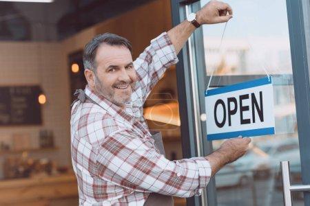bartender hanging open sign on door