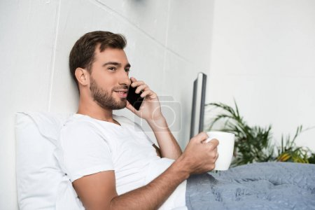 Photo for Attractive young man in white t-shirt sitting in bed with porcelain cup and talking on smartphone - Royalty Free Image