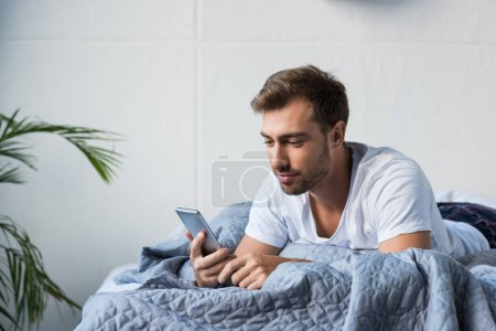 Man in bed using smartphone