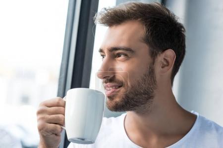 Photo pour Souriant jeune homme portant des commandes de t-shirt blanc par la fenêtre avec une tasse de café - image libre de droit