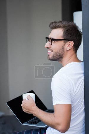 man holding laptop and coffee