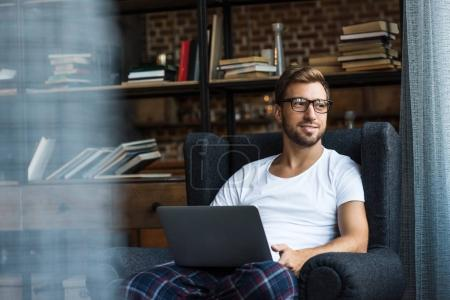 Photo for Smiling young man in home clothes and glasses, sitting in armchair and using laptop - Royalty Free Image