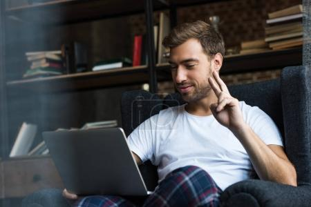 man using laptop and showing peace