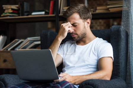 Tired man using laptop