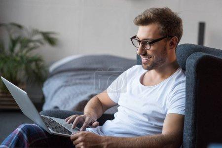 Smiling man in armchair using laptop