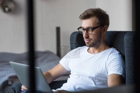 Man in armchair using laptop