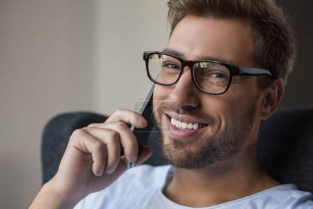 Smiling man talking on smartphone