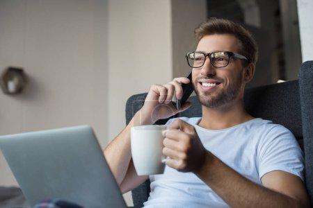Photo pour Jeune homme parle sur smartphone tout en étant assis dans le fauteuil avec une tasse de café et portable - image libre de droit