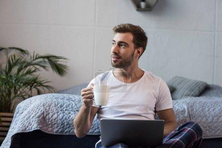 Photo pour Jeune homme assis sur le sol dans sa chambre avec ordinateur portable et tasse de café - image libre de droit