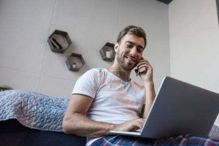 Man on phone using laptop