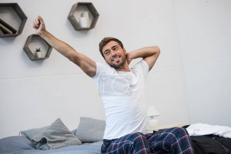 Smiling man stretching on bed