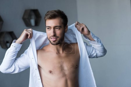 man putting on shirt