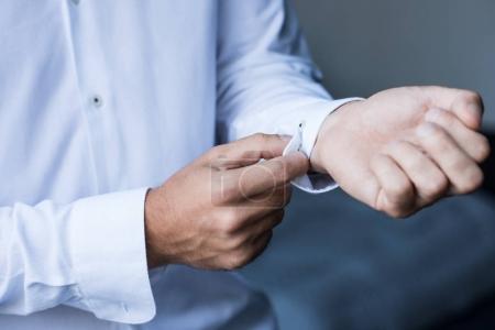 Photo pour Plan recadré d'un homme boutonnant les poignets de sa chemise blanche - image libre de droit
