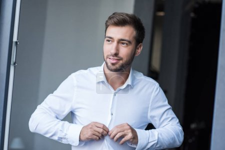 man buttoning up shirt