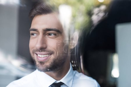 Photo for Portrait shot of a young smiling businessman in white shirt and tie, looking out the window - Royalty Free Image