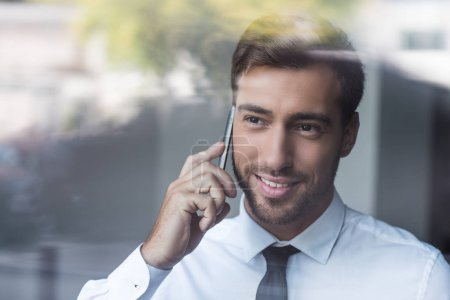 Smiling businessman talking on smartphone