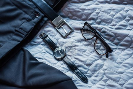 Photo for Composition with black classic suit, belt, glasses and wristwatch on bed - Royalty Free Image