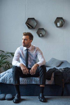 Photo pour Jeune homme d'affaires assis sur le lit en tenue formelle et chaussures en cuir - image libre de droit
