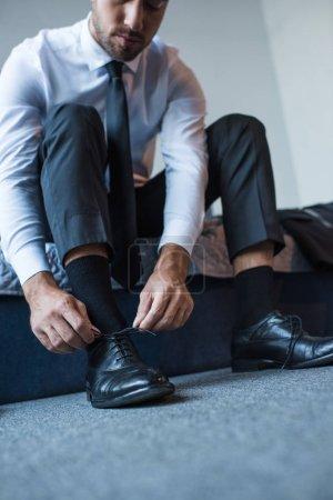 Photo pour Jeune homme d'affaires assis sur le lit et attachant lacets de ses chaussures en cuir noir - image libre de droit