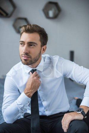 Photo pour Jeune entrepreneur en chemise blanche, redressant sa cravate et à la recherche de côté - image libre de droit