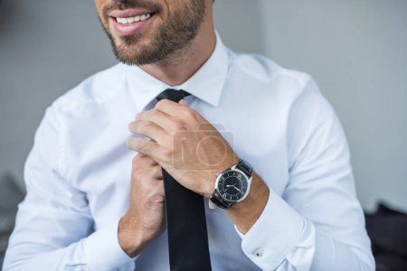 businessman putting on tie