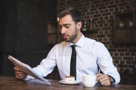 businessman at cafe reading newspaper