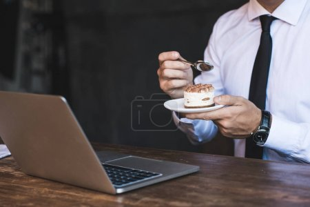 Businessman with laptop and cake