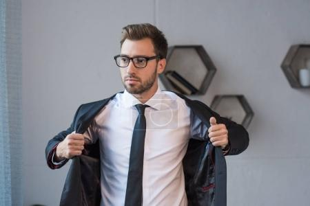 businessman putting on blazer