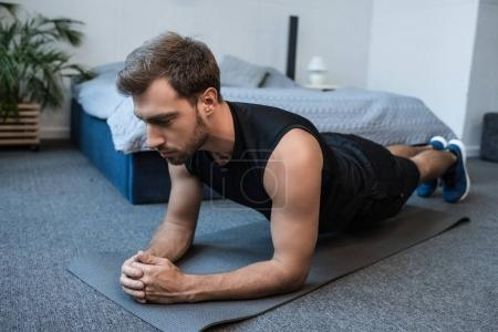 Man planking in bedroom